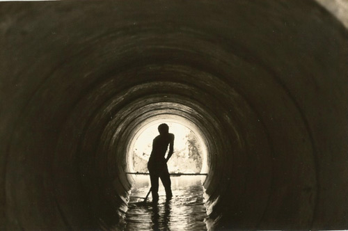 Worker in a tunnel water piping system